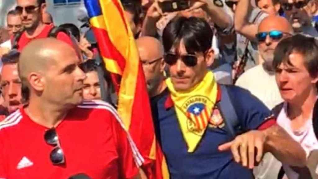El joven de la estelada (derecha) agrede al agente de la Guardia Civil, de camiseta roja (izquierda).
