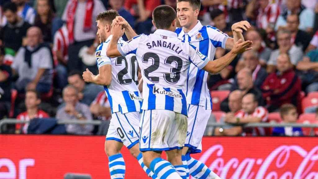 Los jugadores de la Real Sociedad se abrazan tras un gol al Athletic