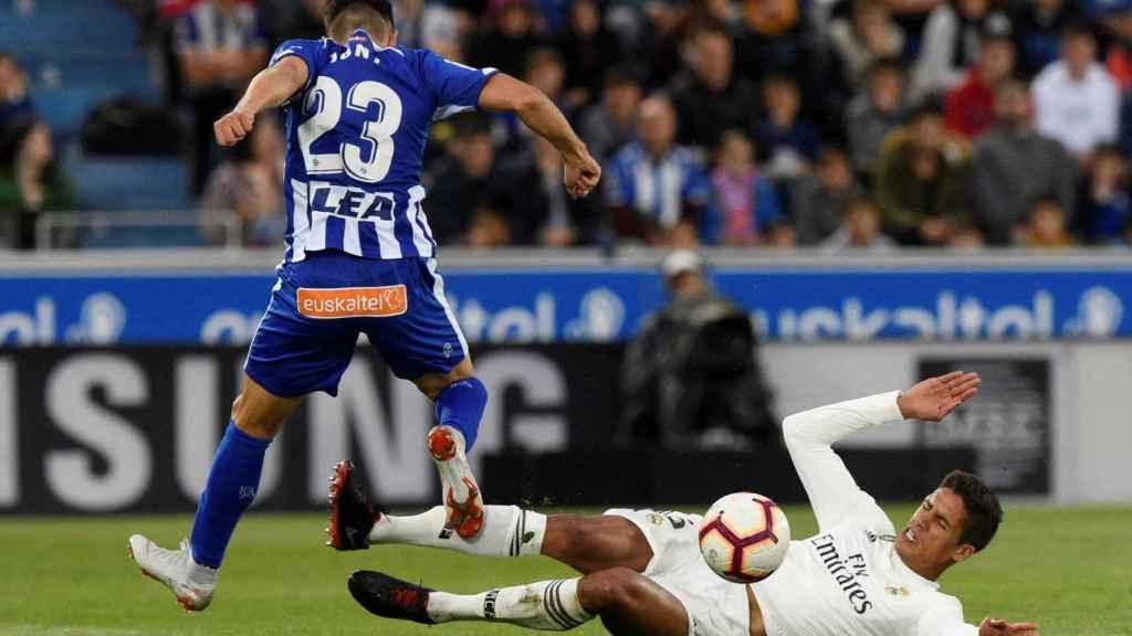 Varane pelea por un balón desde el suelo ante un jugador del Alavés