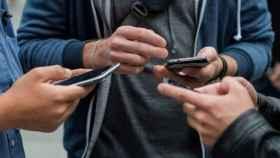 Un grupo de personas maneja sus teléfonos móviles.