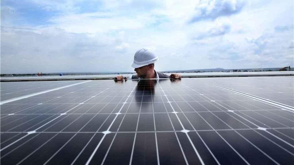 Un trabajador instala una placa en un parque fotovoltaico.
