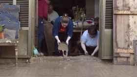 Dos vecinas tratan de achicar agua en las inundaciones de Mallorca.
