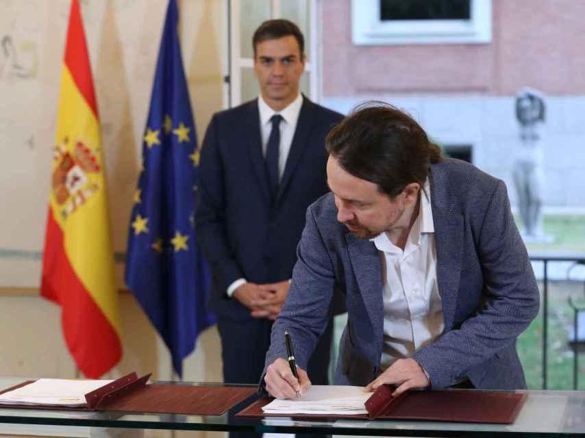 Iglesias firma el acuerdo con Sanchez en la Moncloa.