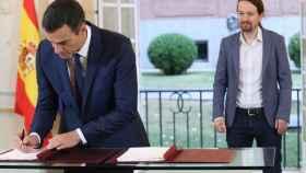 Pedro Sánchez firma el acuerdo en presencia de Pablo Iglesias.
