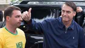 Jair Bolsonaro, junto a su hijo, saluda a los seguidores ante de votar en Río de Janeiro.