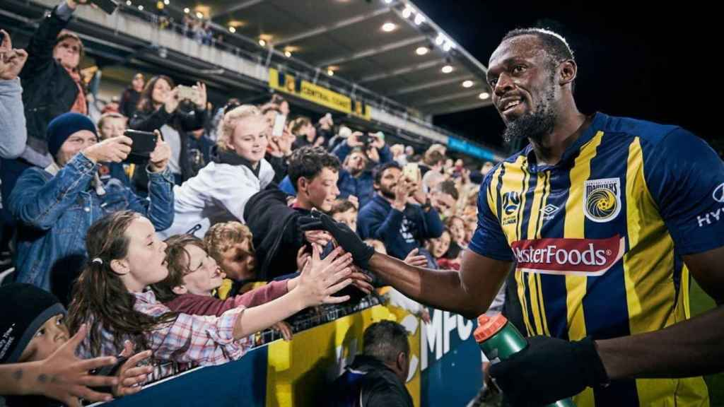Usain Bolt saluda a varios aficionados.