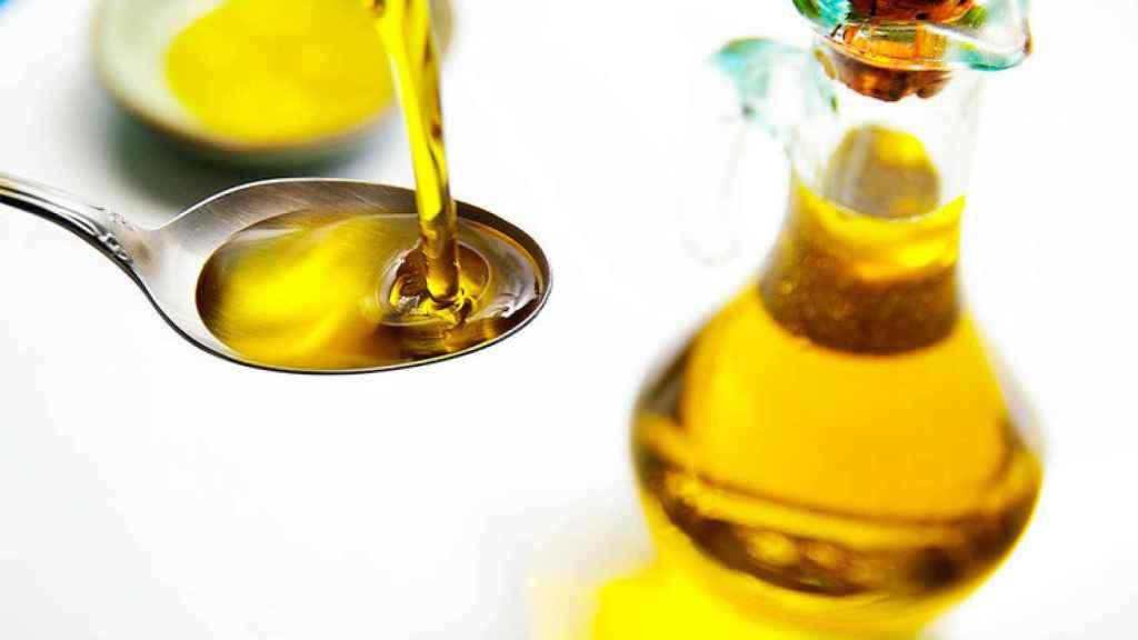 Un chorro de aceite de oliva cae encima de una cuchara.
