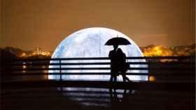 Una pareja pasea cerca de un modelo iluminado del satélite articial