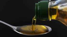 Un chorro de aceite de oliva se escurre a través de una cuchara.