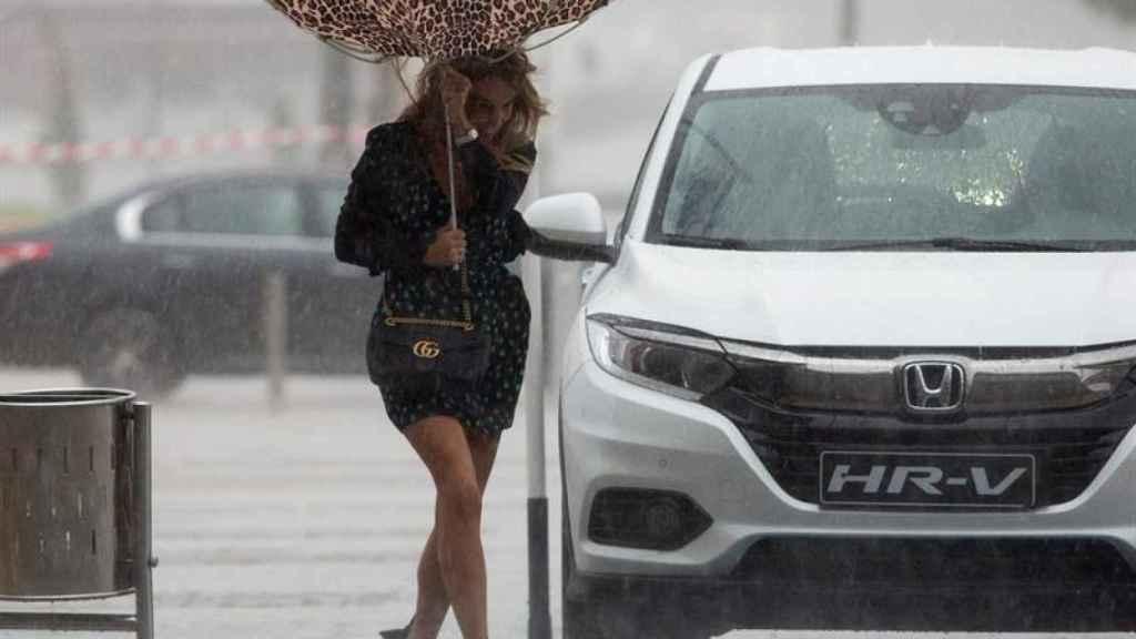 Una mujer sujeta el paraguas intentando que no se le vuele debido al viento y a la lluvia en Málaga.