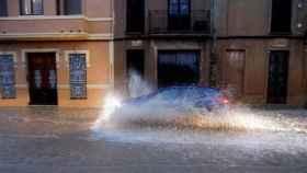 Un vehículo circula por una calle anegada de Valencia.