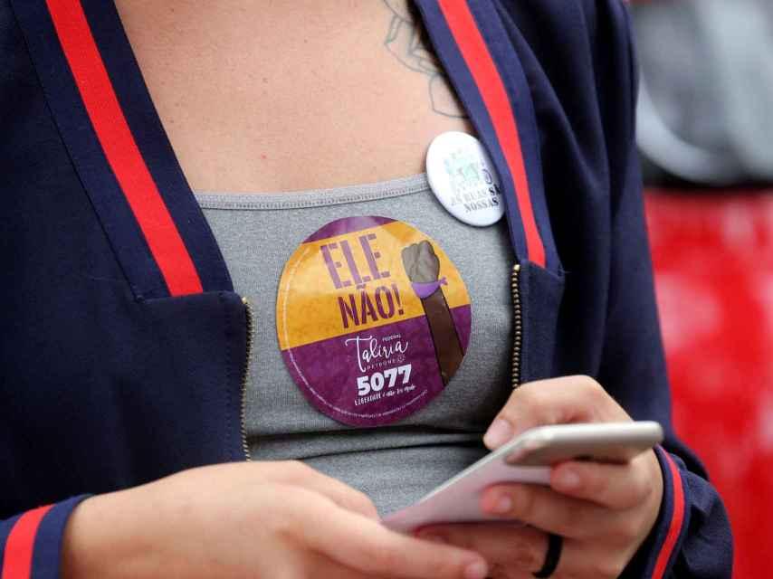 Una chica con una pegatina anti Bolsonaro mira el móvil.