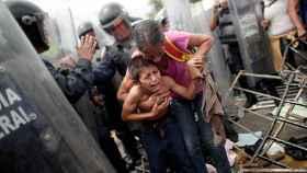 Una migrante hondureña protege a su hijo, después de cruzar la frontera de México.