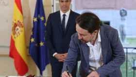 Pablo Iglesias firma el acuerdo con Pedro Sánchez en la Moncloa.