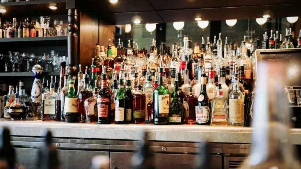 La barra de un bar repleta de bebidas alcohólicas.