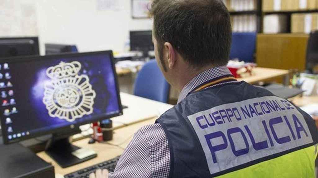 Un agente de Policía Nacional trabajando ante un ordenador.