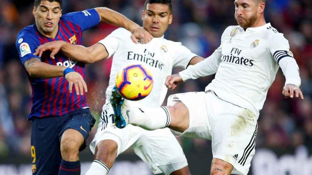 Sergio Ramos y Casemiro pelean un balón con Luis Suárez