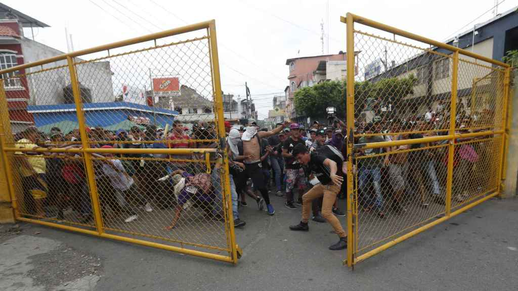 Migrantes hondureños rompen la valla fronteriza entre Guatemala y México.