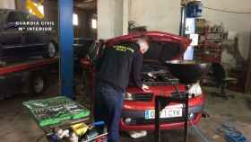 Un guardia civil inspecciona un coche durante una intervención en un taller