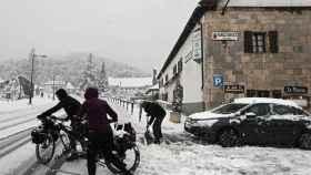 Una pareja de turistas se disponen a continuar su camino en bicicleta en Roncesvalles (Navarra).