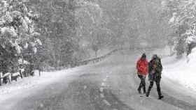 Dos personas caminan bajo una intensa nevada en Roncesvalles.
