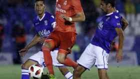 Karim Benzema, entre los jugadores del Melilla durante el partido