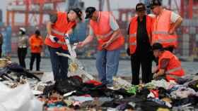 Los investigadores buscan entre los destrozos del avión.