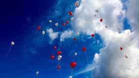 Un hermoso cielo azul lleno de nubes blancas y globos.