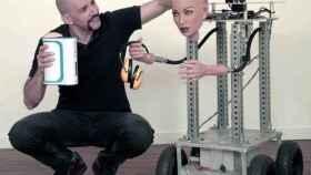 Brian Sloan con las manos ocupadas: el 'Autoblow' en la mano derecha y el robot prototipo en la izquierda.