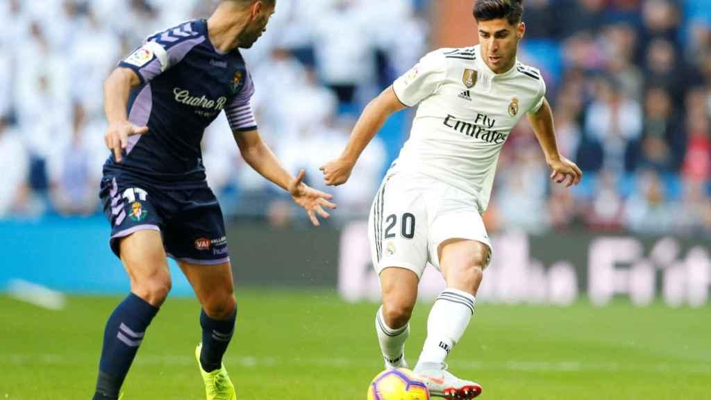 Marco Asensio pasa un balón con un jugador del Valladolid frente a él