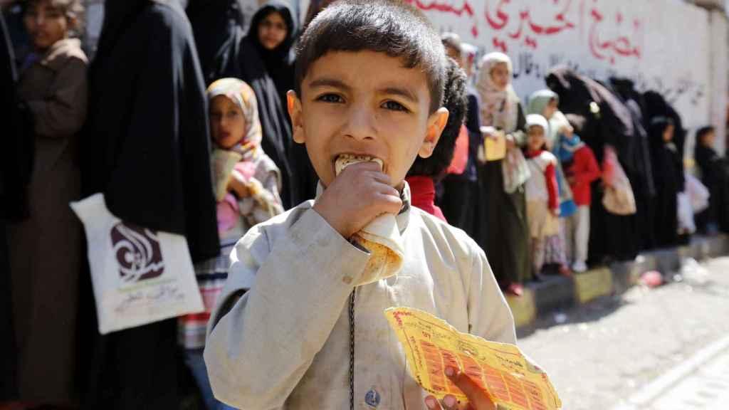 Menor yemení con comida proporcionada por ONG.