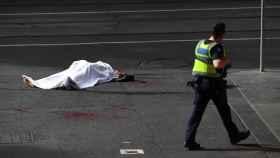 El cadáver de una víctima yace sobre el asfalto tras el ataque.