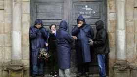 Los turistas bajo la lluvia esta mañana en Santiago de Compostela.
