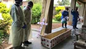 Trabajadores de salud preparándose para llevar a cabo un entierro seguro.