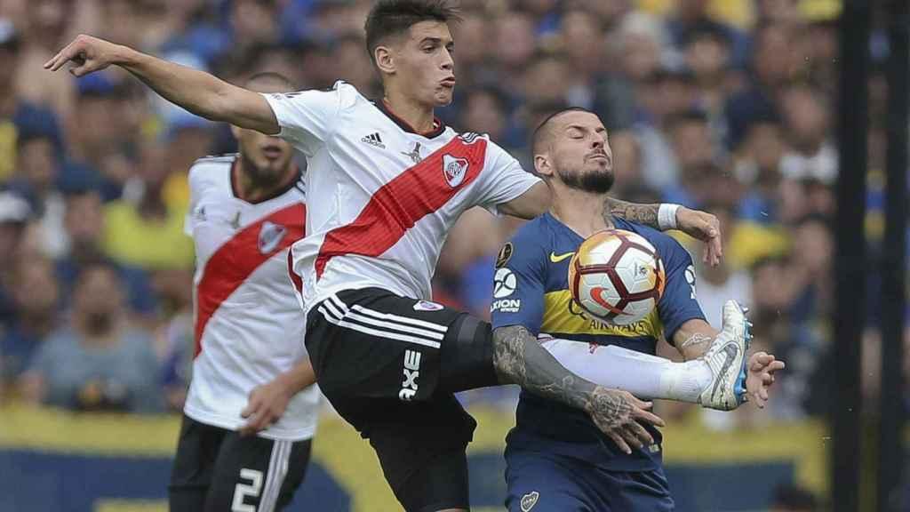 El jugador Dario Benedetto de Boca Juniros disputa la pelota con Exequiel Palacios de River Plate