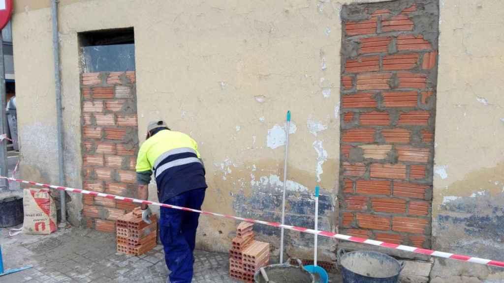 Un obrero tapia los accesos a la casa okupa donde vivían los detenidos