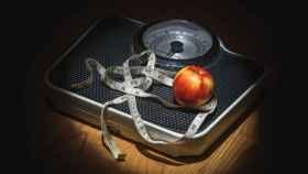 Una manzana rodeada por una cinta métrica encima de una báscula.