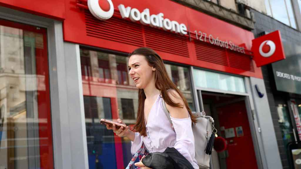 FILE PHOTO: A woman holds a phone as she passes a Vodafone  store in London