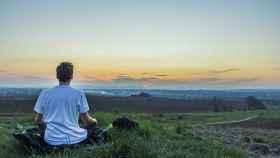 Un joven realiza su sesión diaria de meditación para estar feliz de verdad.