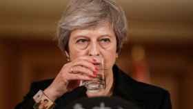 May da un trago durante su comparecencia este jueves en Downing Street.