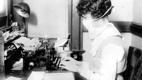 Mujer con mascarilla por la gripe española.