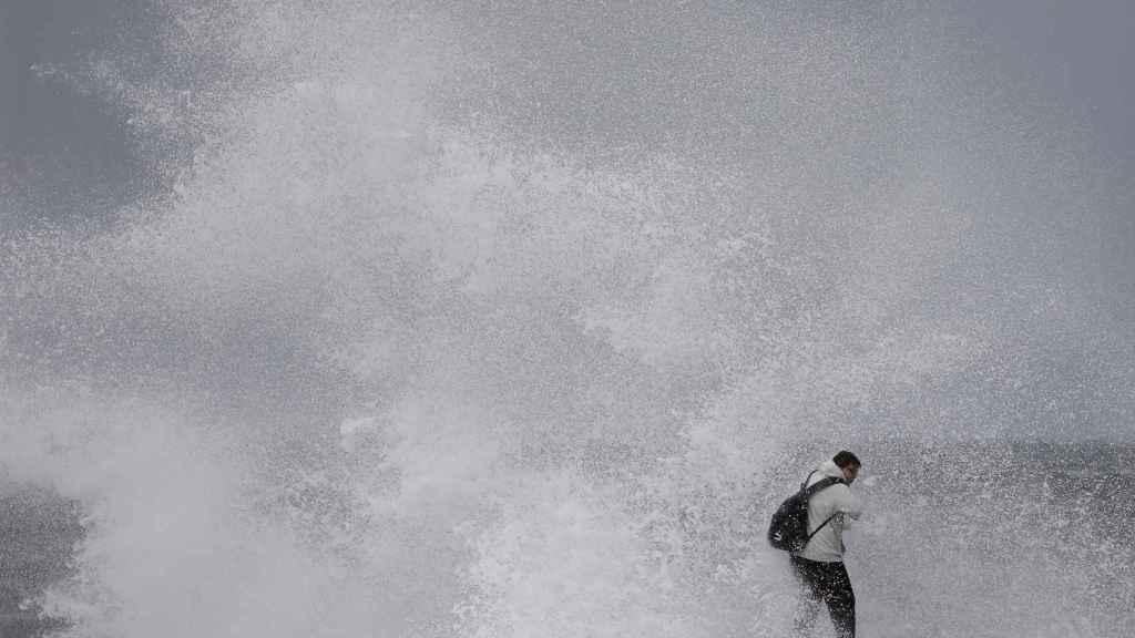 Un ciudadano se enfrenta al fuerte oleaje en Barcelona