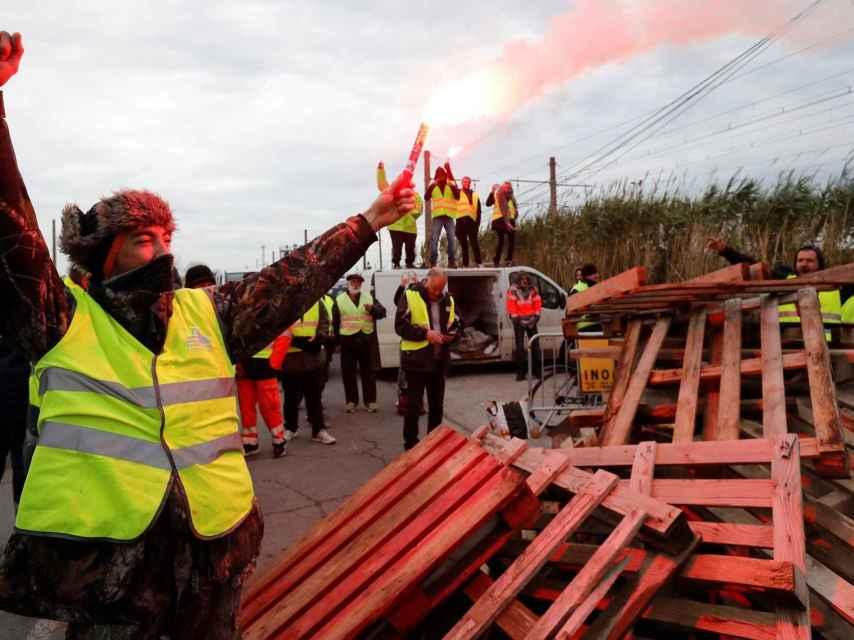 Manifestantes vestidos con chalecos amarillos bloquean el acceso a la refinería de Frontignan.