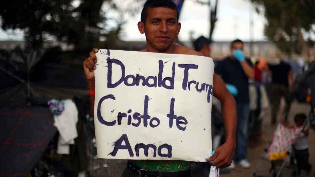 Un migrante muestra una pancarta con el lema 'Donald Trump, Cristo te ama', en Tijuana.