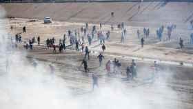 Varios migrantes de la caravana huyen del gas lanzado por la Policía de EEUU en la frontera.