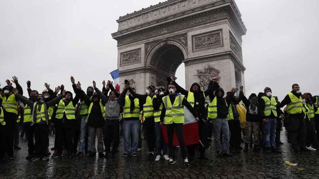 Los 'chalecos amarillos' forman ante la policía en el Arco del triunfo de París.