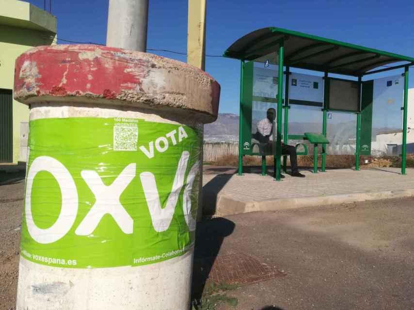 Propaganda electoral de Vox delante de una parada de autobús en la que esperaba sentado un inmigrante subsahariano.