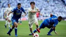 Juan Ramón Ruan y Jilmar Torres intentan arrebatar el balón al defensa del Real Madrid Alvaro Odriozola