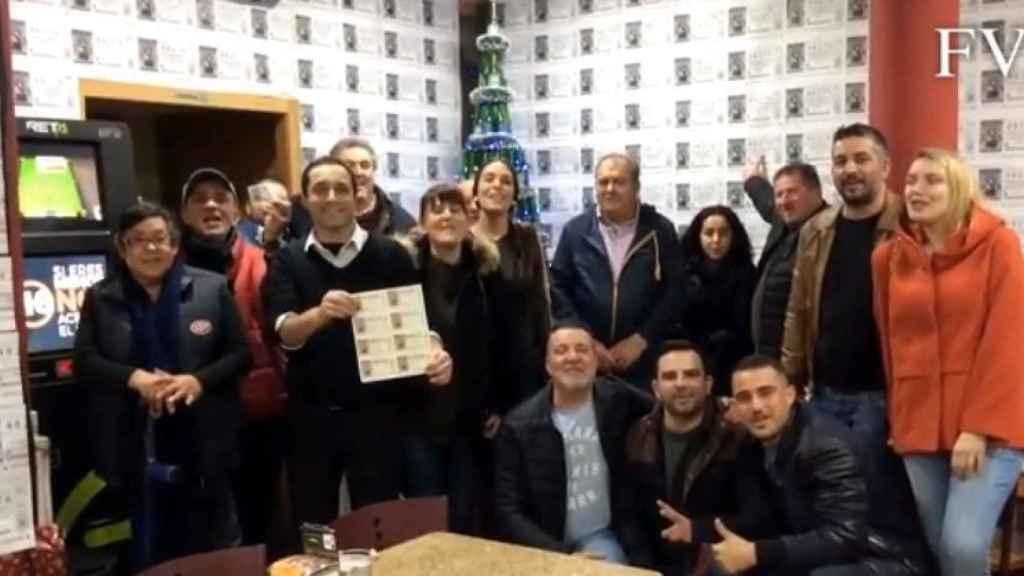 José Ramón, sujetando los décimos, junto a los clientes en el bar Varillas.