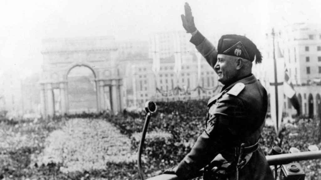 Benito Mussolini haciendo el saludo fascista en un acto.